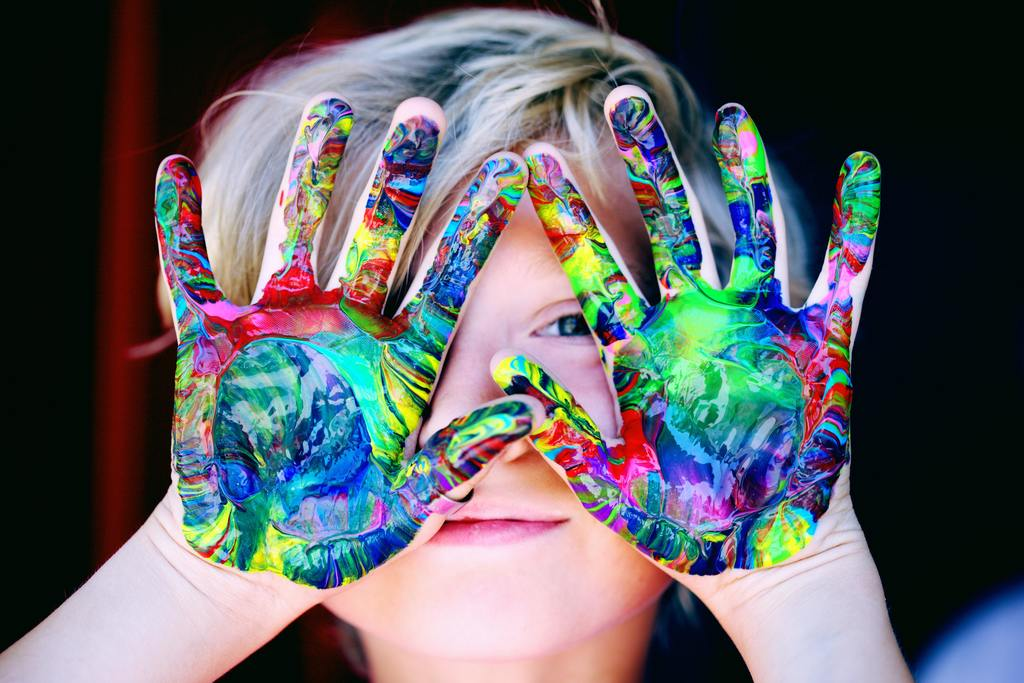 Child holding finger paint covered hand up
